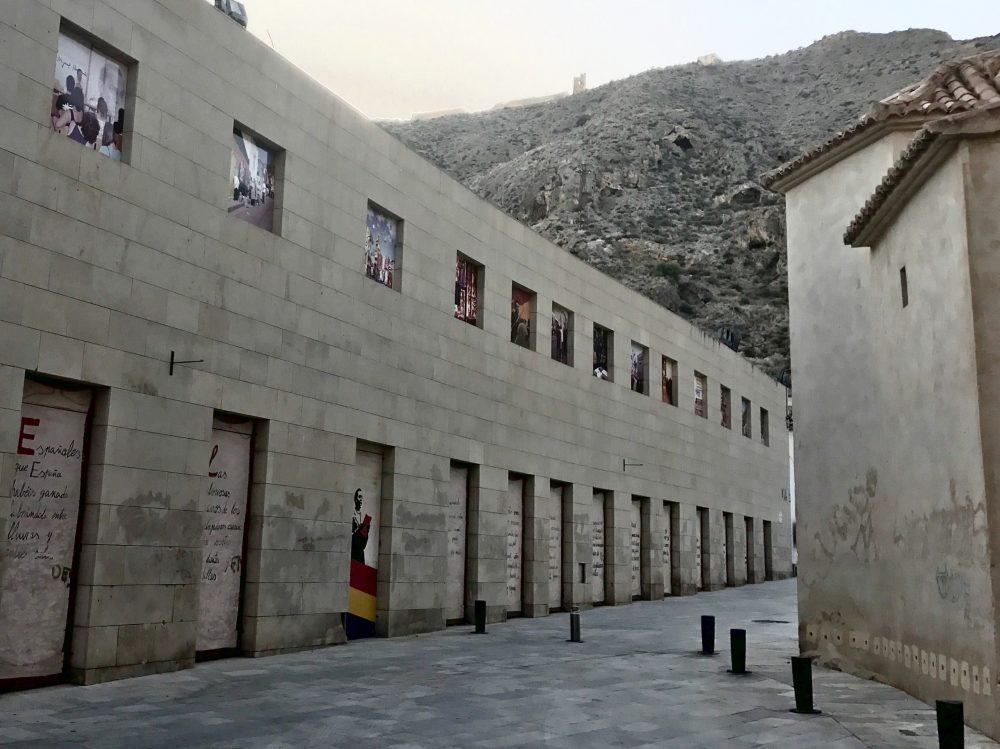 Orihuela - Cestou k turistickému informačnému centru, farebný múr oddeľuje staré domy od námestia